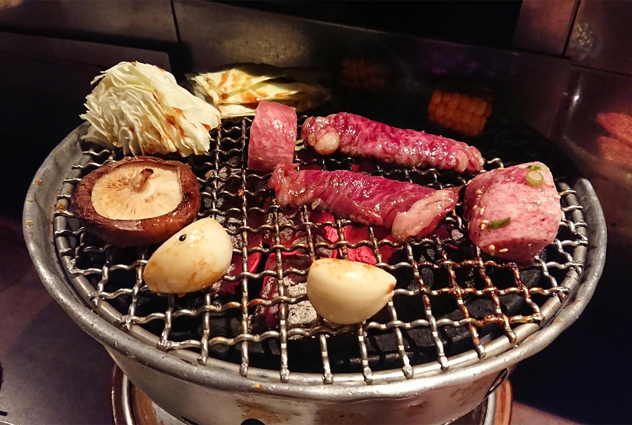 網の上で焼いている肉と野菜の写真
