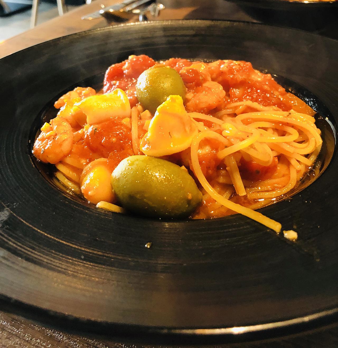 魚介とオリーブを使ったトマトソーススパゲティの写真