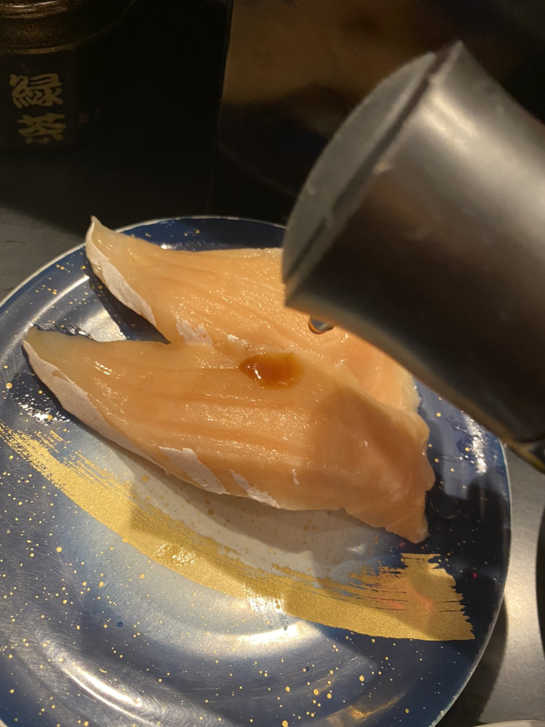 ネタに醤油をかける写真