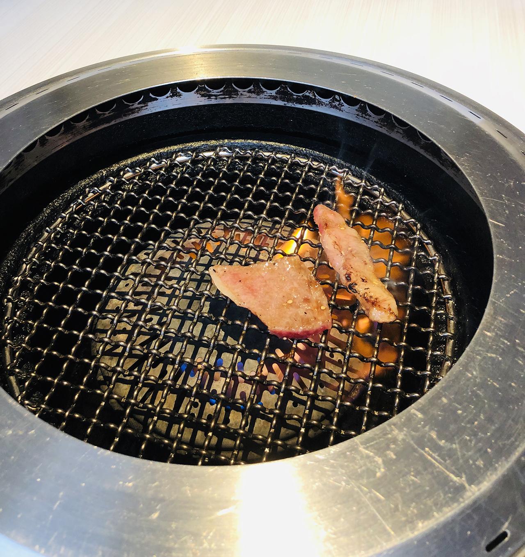 お肉を網で焼いている様子の写真